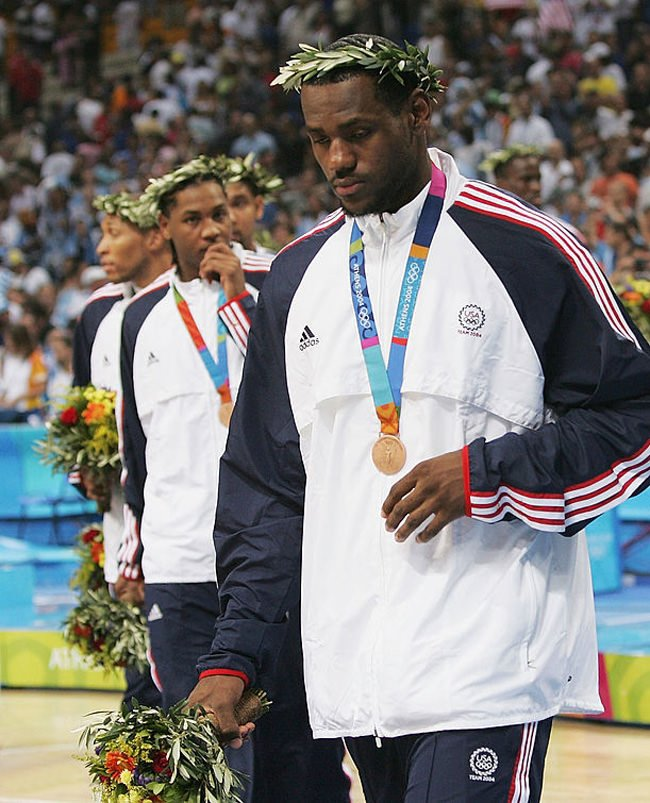 ATHENS - AUGUST 28: LeBron James #9, Carmelo Anthony #8 and Allen Iverson of the United States walk off the court after they receive the bronze medal for men's basketball during ceremonies on August 28, 2004 during the Athens 2004 Summer Olympic Games at the Indoor Hall of the Olympic Sports Complex in Athens, Greece. (Photo by Jamie Squire/Getty Images) *** Local Caption *** LeBron James;Carmelo Anthony;Allen Iverson