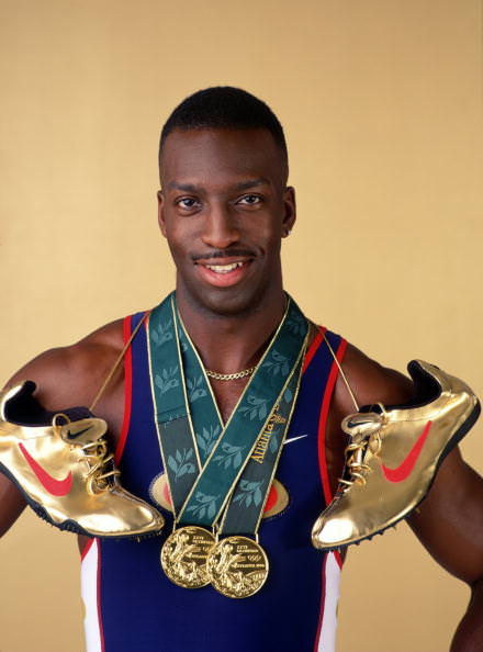 """12 Aug 1996: Sprinter Michael Johnson poses for a studio portrait with his two Olympic gold medals and his golden running shoes. Johnson became the first man to complete the Olympic """"Golden Double"""" after winning both the 200m and 400m finals at the 1996C"""