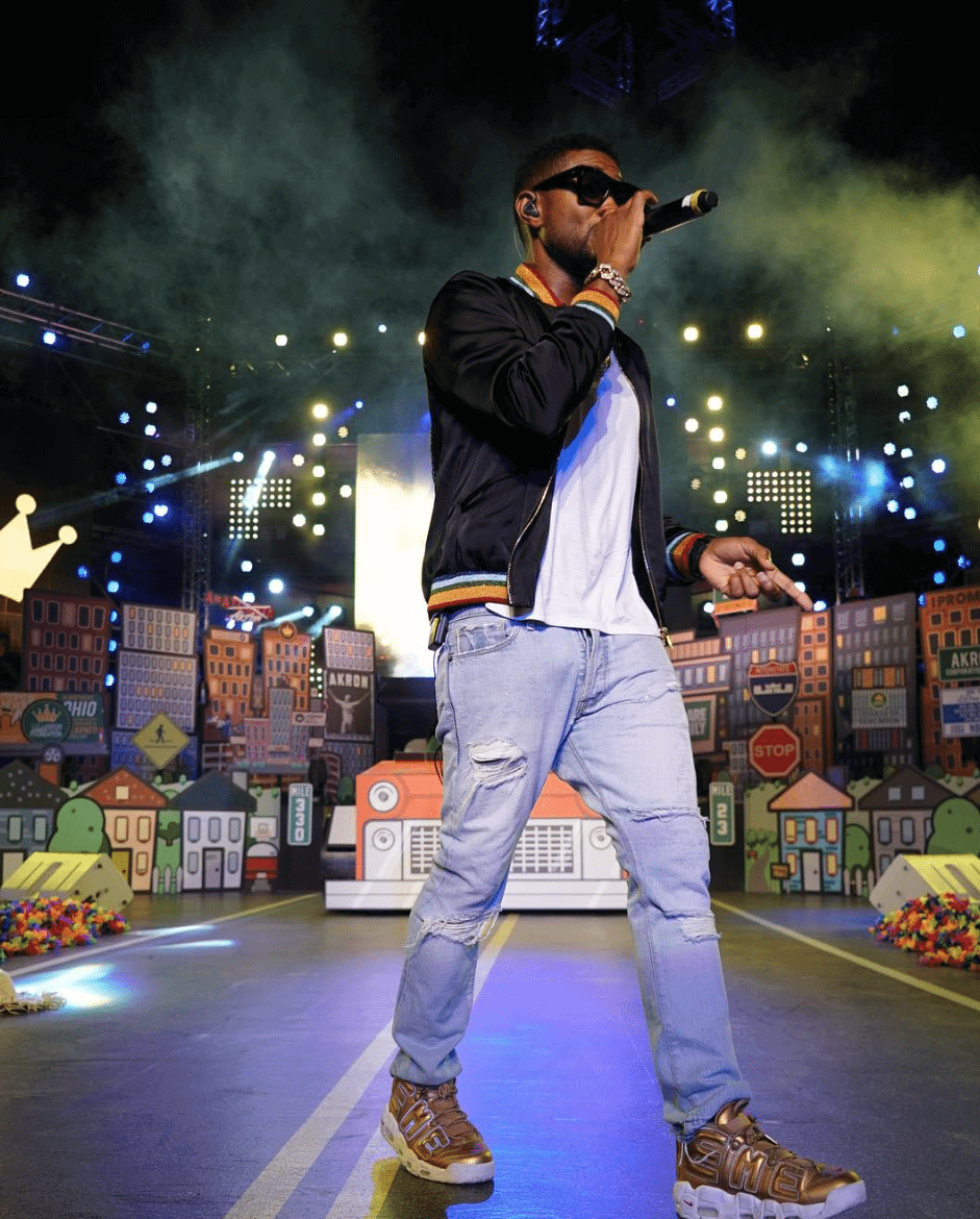Usher uses the Supreme x Nike Air More Uptempo to match the hues on his bombers jacket.