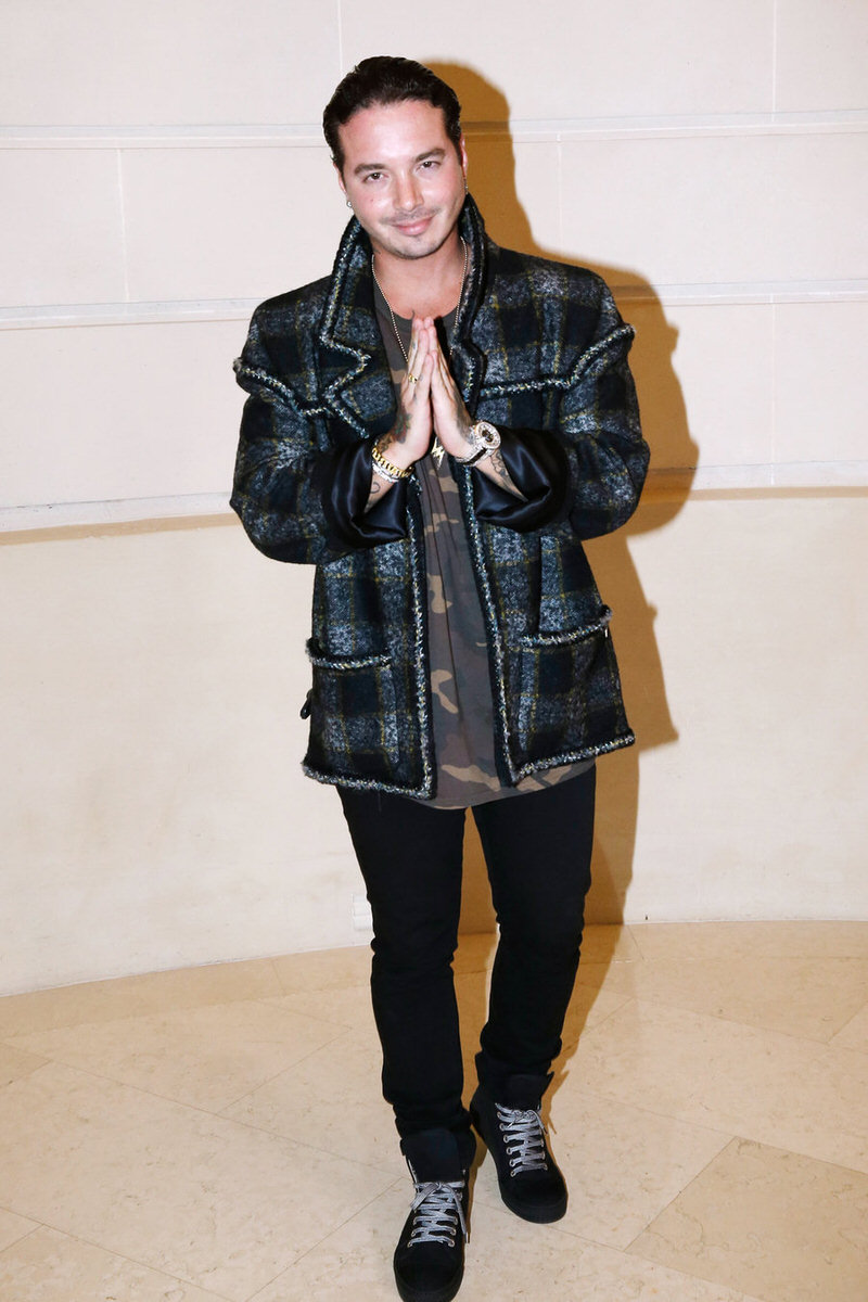 J Balvin experiments with merging plaid and camo tones with his jacket and tee combo.