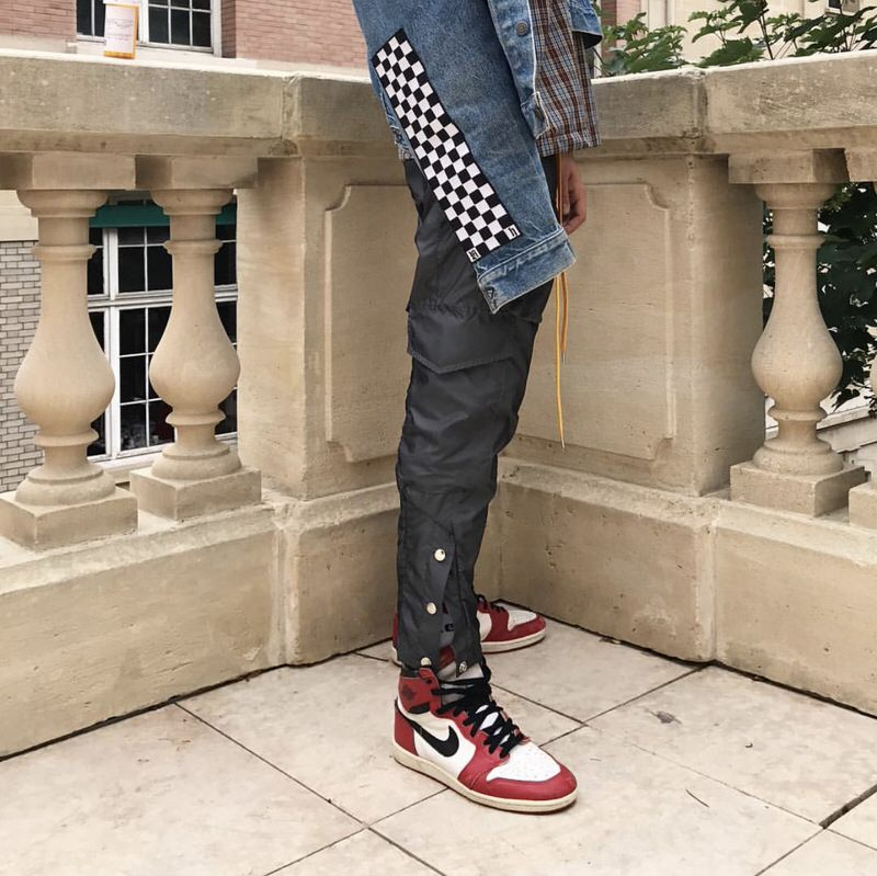 Updated classics. Rhude adds a checkerboard print to their denim trucker jacket and a tear away component to their drawstring warm-up pants, while the '85 Jordan 1s keep the overall look timeless and casual.