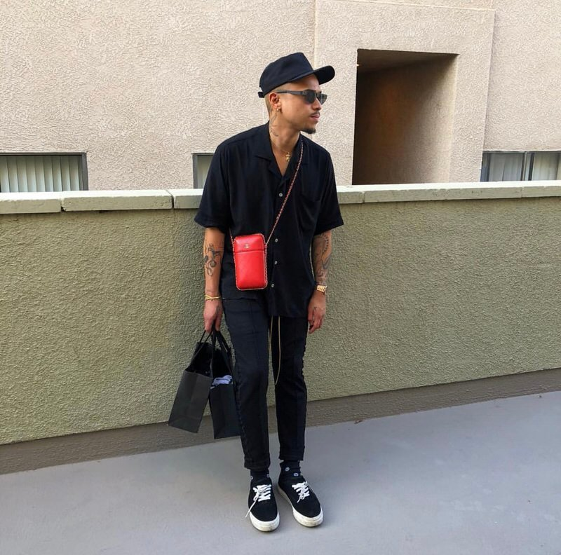 Simply sophisticated. The red cross-body bag is a standout essential that makes Rhuigi's all-black kit pop that much more.