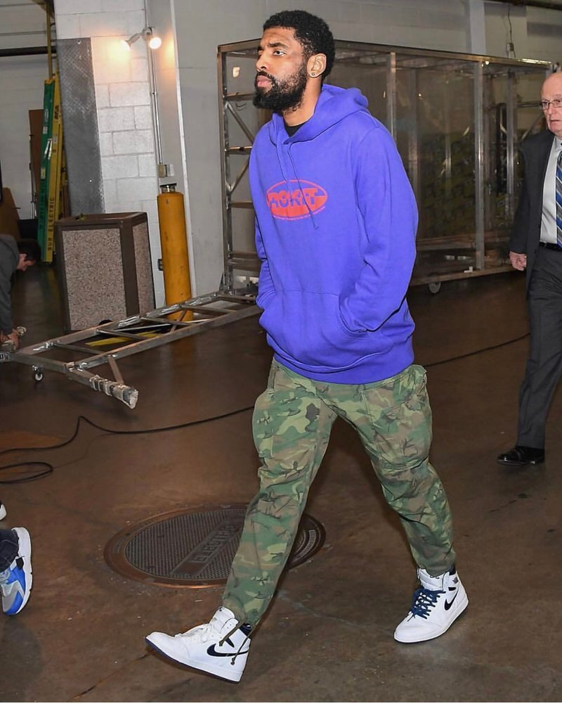 Kyrie pairs a retro inspired Rockit hoodie with Jordan 1s and cargo pants.