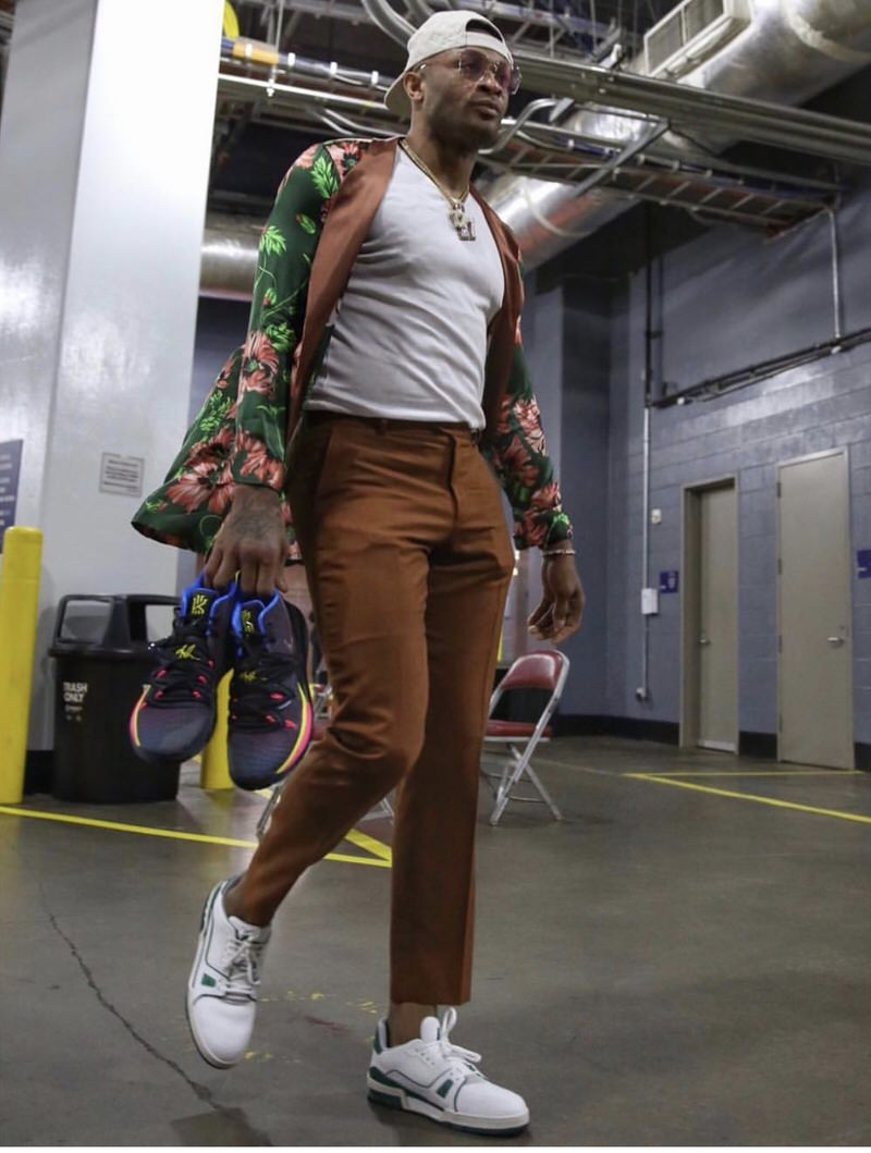 PJ Tucker wears Palm Angels Jacket with cropped trousers and Louis Vuitton LV Trainers.