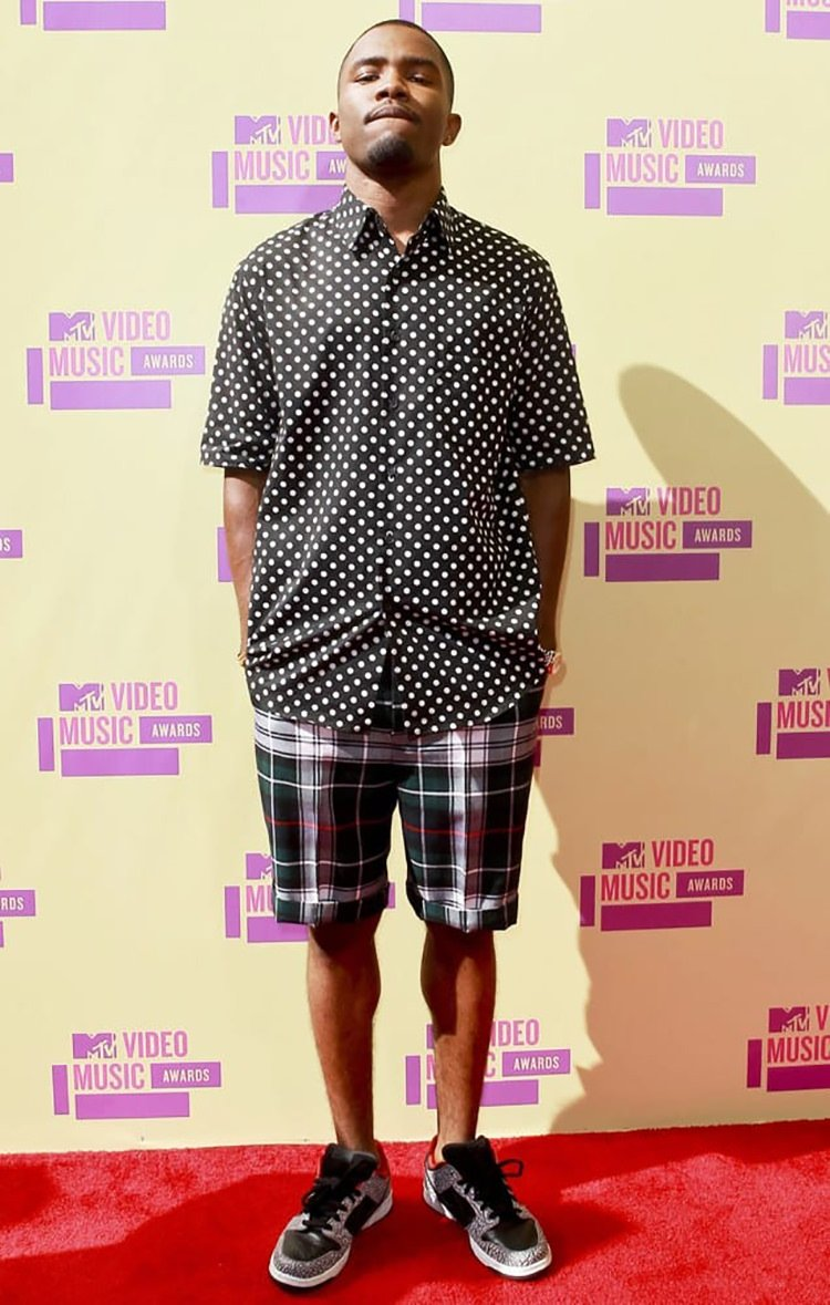 Frank Ocean gets pattern heavy with his polka-dot shirt, plaid shorts, and Supreme x Nike SB Dunk Low.
