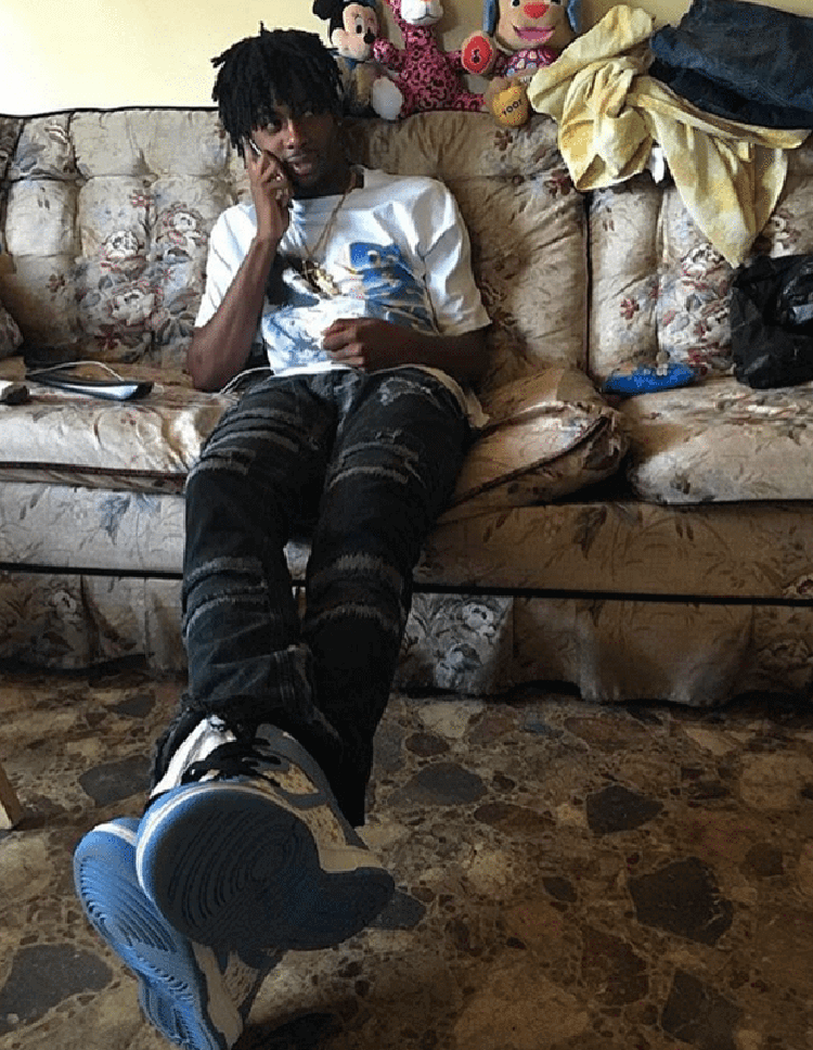 Playboi Carti takes a simple approach by teaming the Supreme x Nike SB Dunk High with thrashed jeans and a graphic tee.