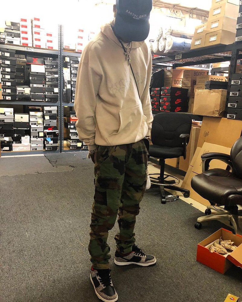 Travis pairs cargo pants with a vintage fitting hoodie and Supreme Dunk Lows.